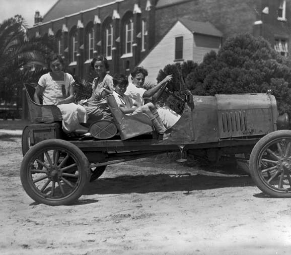 Students sitting in a Model T Ford car in front of Smathers Library